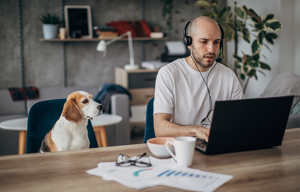 Man working from home with his faithful dog at his side
