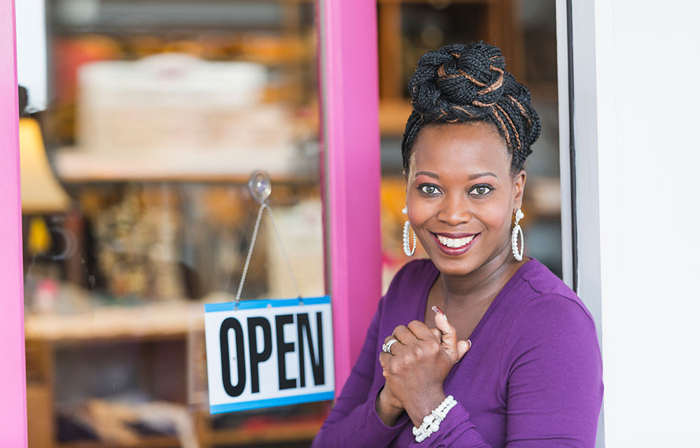 Woman happy by her sign that Business is Open